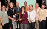 CCME President Joycelyn Groot presented 2013 Institution Award. Seen in the front row left to right: Mindy Boenning, communication and development coordinator, Joycelyn Groot, CCME president, Linda Frank, Desiree Drindak, Susan Bruce. Seen in the back row left to right, William Yaeger, Charles Van Vorst, and William Mayeaux.