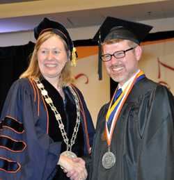 Acting President Meg Benke with student speaker and Chancellor's Award for Student Excellence recipient Sean Coffman immediately after Coffman was presented with the college medallion.