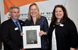 Northeast Center Dean Gerry Lorentz and Acting President Meg Benke, center, present Director of Academic Support Lisa D'Adamo-Weinstein, at right, with the Chancellor's Award for Excellence in Professional Service.