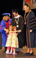 Master's recipient Michael DeMasi of Clifton Park, is joined on stage by his daughters as Tai Arnold, acting dean of the School for Graduate Studies, left and Acting President Meg Benke, right, look on.