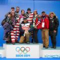 Erin Hamlin '11 surrounded by her parents, brothers and friend. Her coach, two-time Olympic medalist and USA Luge program director Mark Grimmett, kneels in front.