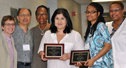 Dianne Ramdeholl, at left and Jaye Jones hold the plaques commemorating their receiving the 2014 AERC Phyllis Cunningham Social Justice Award. The members of the award committee, Lisa Baumgartner, Luis Kong and Doris Flowers stand to Ramdeholl's left and Vanessa Sheared stands with Jones. AERC 2014 was held on the Harrisburg campus of Penn State University. Photo © Harrisburg State University
