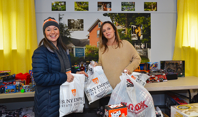 SUNY Empire employee Janet Aiello-Cerio, at left, drops off holiday gifts to Lindsay Duma, a volunteer with the Franklin Community Center.