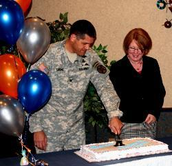 "Colonel Bryan Laske, garrison commander at Fort Drum, cuts the cake emblazoned with ""A tradition of excellence in education,"" the event celebratory theme, as Nikki Shrimpton, dean of undergraduate studies for SUNY Empire, looks on."