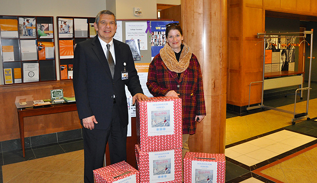 Executive Vice President for Administration Joseph L. Garcia, a retired lieutenant colonel and 28-year veteran of the U.S. Air Force, stands with Librarian Sara Hull in the lobby of 2 Union Ave., Saratoga Springs, N.Y., as cards for the Holidays for Heroes program were collected.