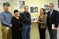 Agnes Zellin '82 and Paul Tick '75, holding the exhibit book, were joined by Dean Gerald Lorenz, far left, Secretary Ginger Schwartz and Tom Mackey, vice provost for academic services, standing far right. Photo/Empire State College