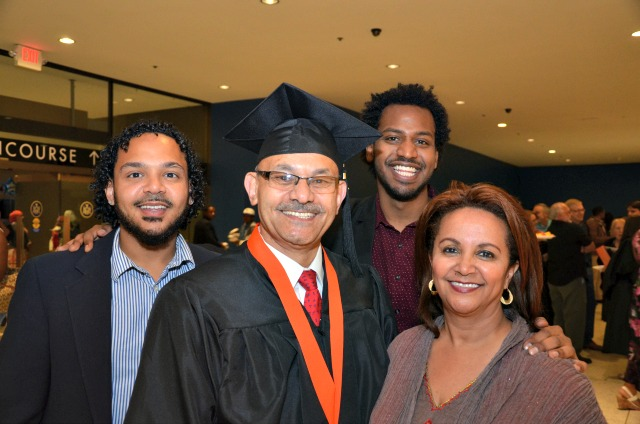 Zekarias Mekonnen surrounded by his wife and two sons at the college Albany commencement event.