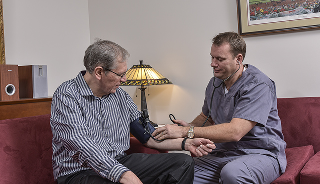 Stat Staff Professionals Founder and CEO David Theobald '13, '17, at left wearing medical scrubs, checks vital signs of former employee Ruffin Pauszek.