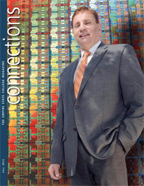 Mike Russo '10, director of government relations for the semi-conductor manufacturer, GlobalFoundries, is pictured in front of a chip disc display - cover of Connections Fall 2012
