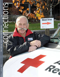 Jim Savitt leaning on a Red Cross vehicle - cover of Connections Spring 2012